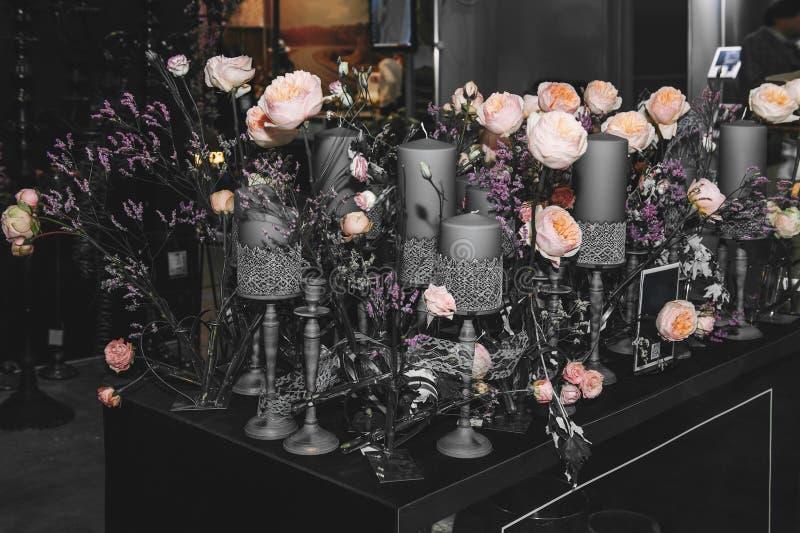 Een reusachtig boeket van mooie Engelse rozen is verfraaid in het binnenland met mooie grijze kandelaars en kaarsen van divers royalty-vrije stock foto