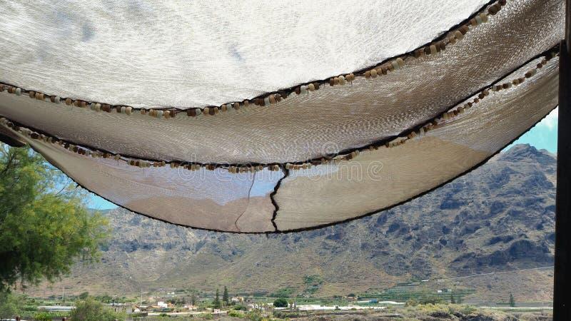 Een reusachtig genaaid visnet aan beide kanten rekte hoogte in de lucht als zonnescherm uit stock foto's