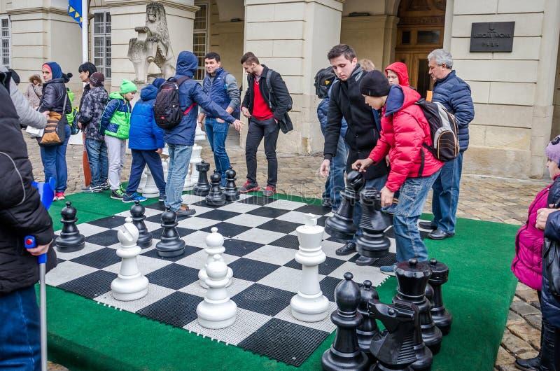 Een reusachtig schaakbord waarop de slag in de toernooienkinderen die met witte en zwarte stukken in openlucht op de straat spele stock foto