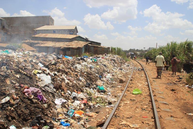 een reusachtige berg van huisvuil en een spoorweg op het slechtste gebied van Nairobi - Kibera stock foto's