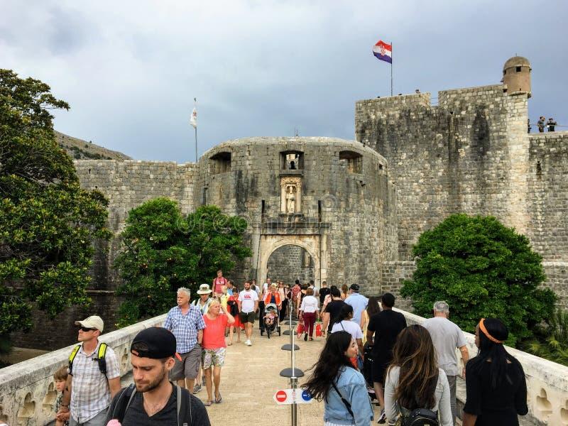 Een reusachtige menigte van toeristen die en door de historische muren van Dubrovnik binnengaan weggaan die de oude stad van Dubr royalty-vrije stock foto