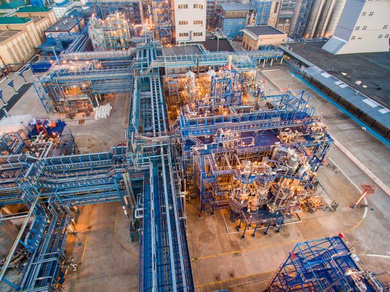 Een reusachtige olieraffinaderij met metaalstructuren, pijpen en distillatie van het complex met het branden lichten bij schemer  stock foto's