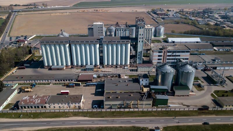 Een reusachtige olieraffinaderij met metaalstructuren, pijpen en distillatie van het complex met het branden lichten bij schemer  stock afbeelding