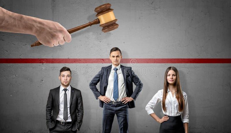 Een reuzehand met een rechtershamer boven drie zakenlui met één van hen die uit boven een rode lijn plakken royalty-vrije stock afbeeldingen