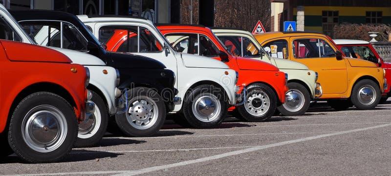 Een rij die van kleurrijk Fiat 500s in een kant van de wegparkeerterrein, wachten aan een auto deel te nemen die zich later verza stock foto