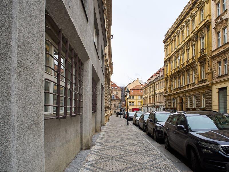 Een rij van auto's aan de kant van de weg door een stoep in een stad met gebouwen worden geparkeerd dat stock fotografie