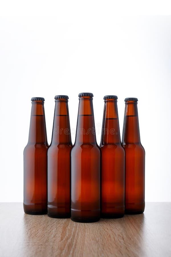 Een rij van bierflessen op witte achtergrond stock foto