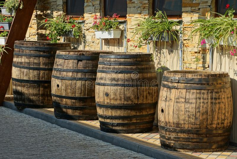 Een rij van bruine houten vaten bevindt zich op de stoep dichtbij de muur met bloempotten en vensters stock foto