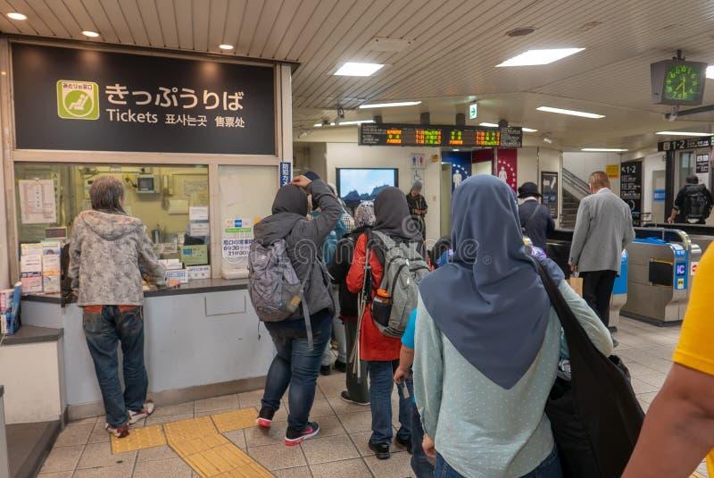 Een rij van de groeps Moslimtoerist bij een kaartjesteller bij scheenbeen-imamiya-Ekimaepost in Osaka, Japan royalty-vrije stock afbeelding