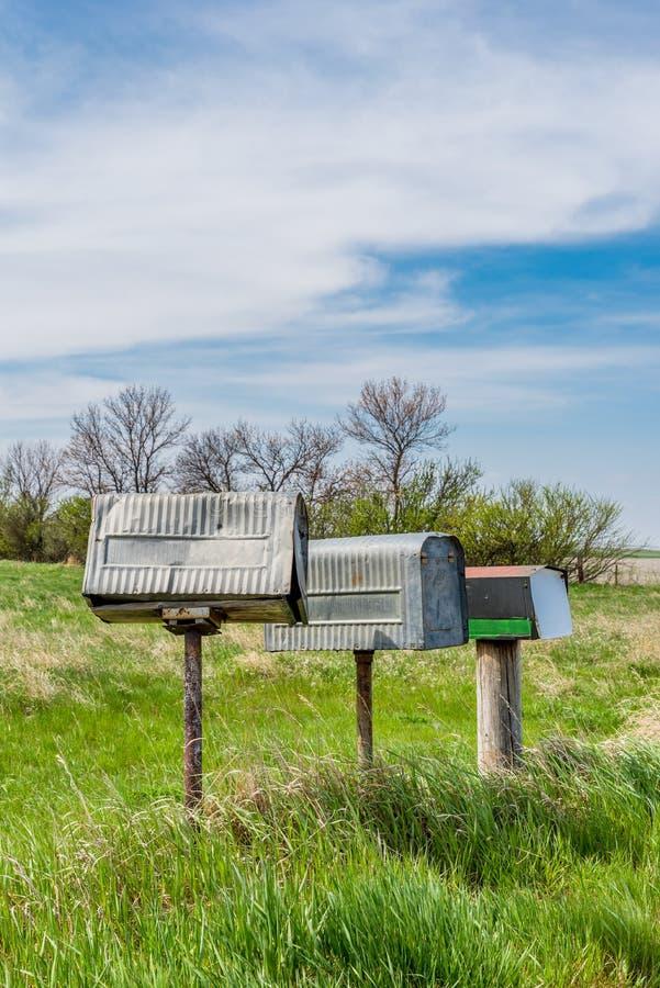 Een rij van drie oude brievenbussen van metaallandbouwers in landelijk Saskatchewan, Canada royalty-vrije stock fotografie
