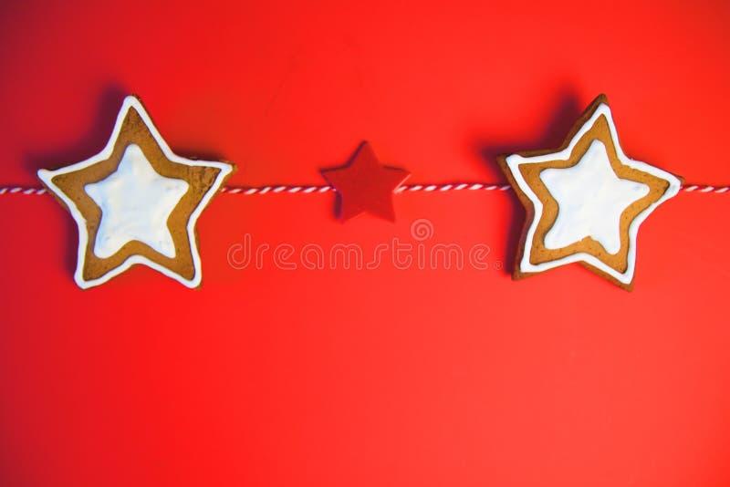 Een rij van drie sterkoekjes De koekjes bonden een rood lint Deze boete handcrafted met de hand en schilderde Koekjes in de vorm stock foto's