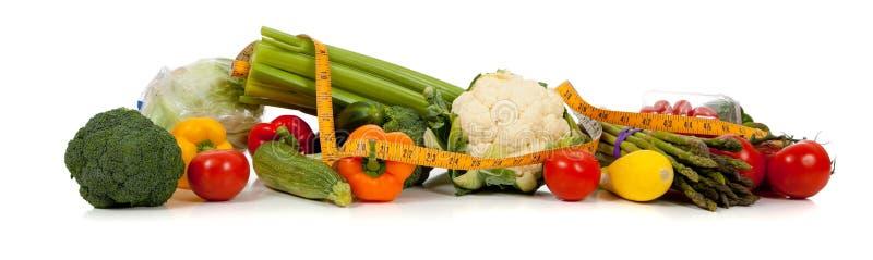Een rij van groenten en een meetlint op wit stock fotografie