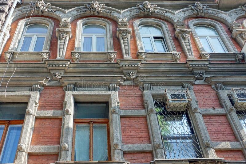 Een rij van oude vensters op een grijze bruine bakstenen muur stock foto