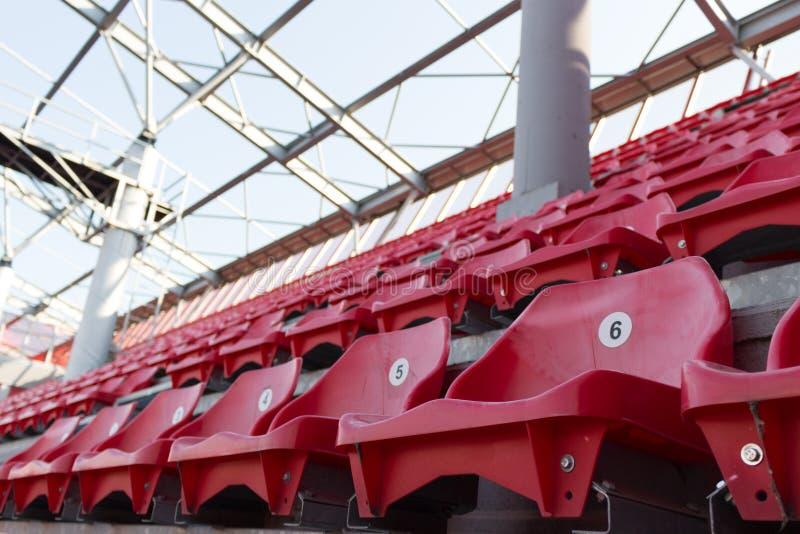 Een rij van rode plastic stoelen op een stadion stock foto's