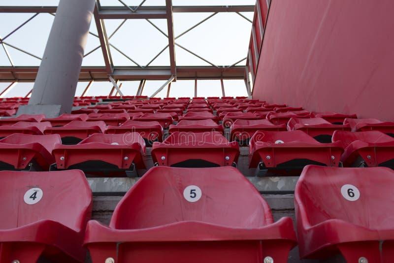 Een rij van rode plastic stoelen op een stadion royalty-vrije stock foto