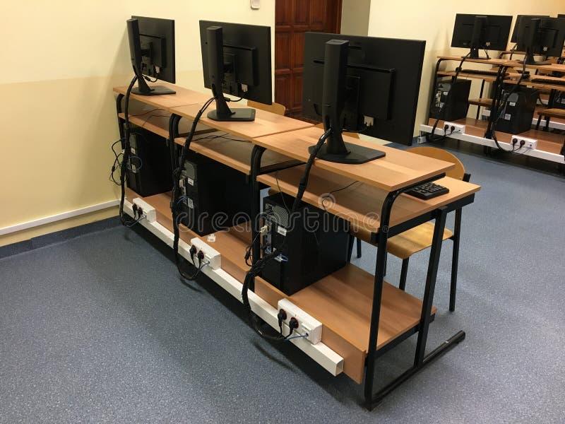 Een rij van stoelen, computers en monitors op de lijst in het lege klaslokaal royalty-vrije stock fotografie