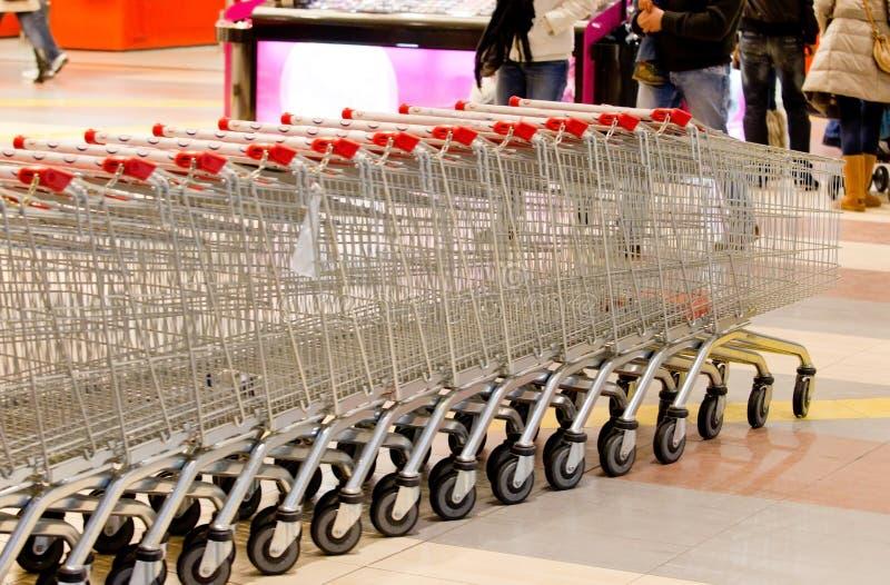 Een rij van vele boodschappenwagentjes van een supermarkt stock afbeelding