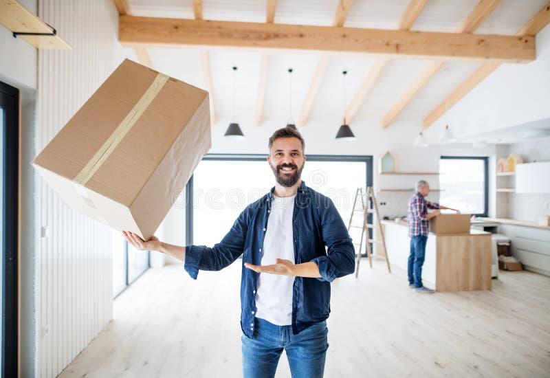 Een rijpe mens die een grote doos in één hand houden wanneer het leveren van nieuw huis royalty-vrije stock foto