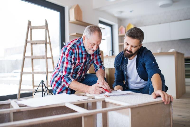 Een rijpe mens met zijn hoger vader het assembleren meubilair, een nieuw huisconcept stock foto