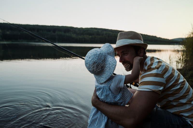 Een rijpe vader met een kleine peuterdochter die in openlucht door een meer vissen stock foto's