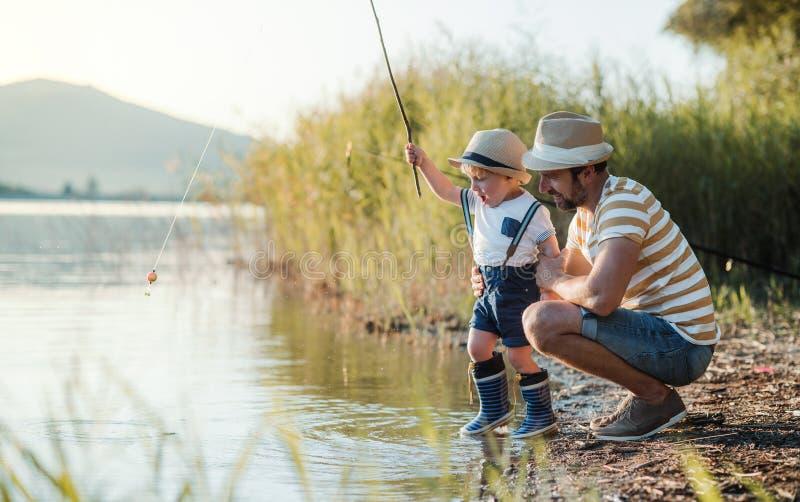 Een rijpe vader met een kleine peuterzoon die in openlucht door een meer vissen stock foto