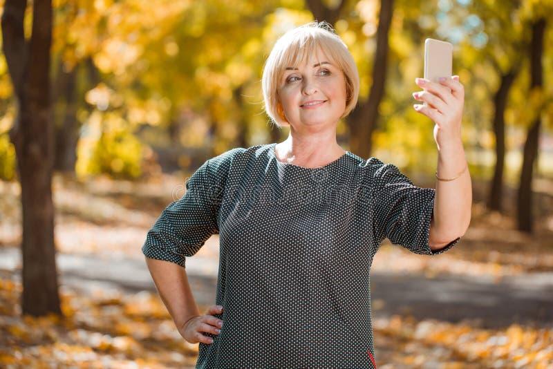 Een rijpe vrouw glimlacht en maakt selfie op de telefoon In het de herfstpark royalty-vrije stock fotografie