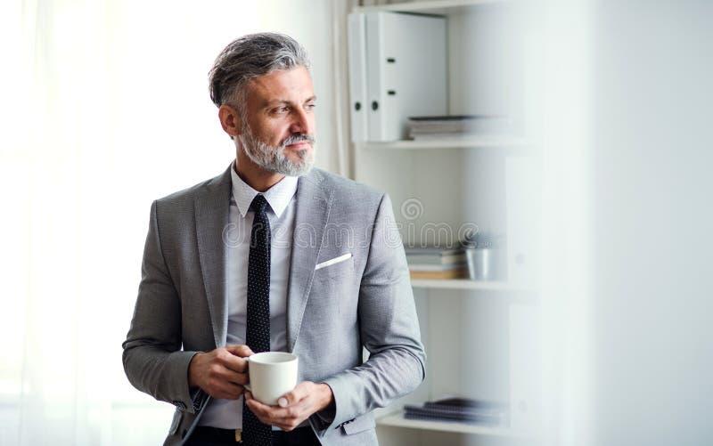 Een rijpe zakenman die zich in een bureau bevinden, die een kop van koffie houden De ruimte van het exemplaar stock foto