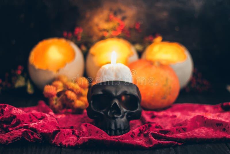 Een rituele Halloween-hekserijscène met kaarsen, de uitstekende doek op de rustieke achtergrond en een eng schedelskelet zien ond stock fotografie