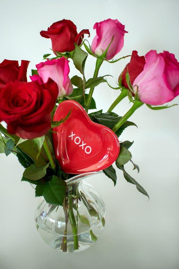 Een rode die valentijnskaart tussen rozen in een vaas wordt geplaatst stock foto