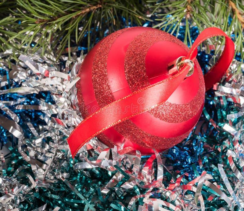 Een rode Kerstboombal onder het klatergoud De achtergrond van het nieuwjaar royalty-vrije stock foto's
