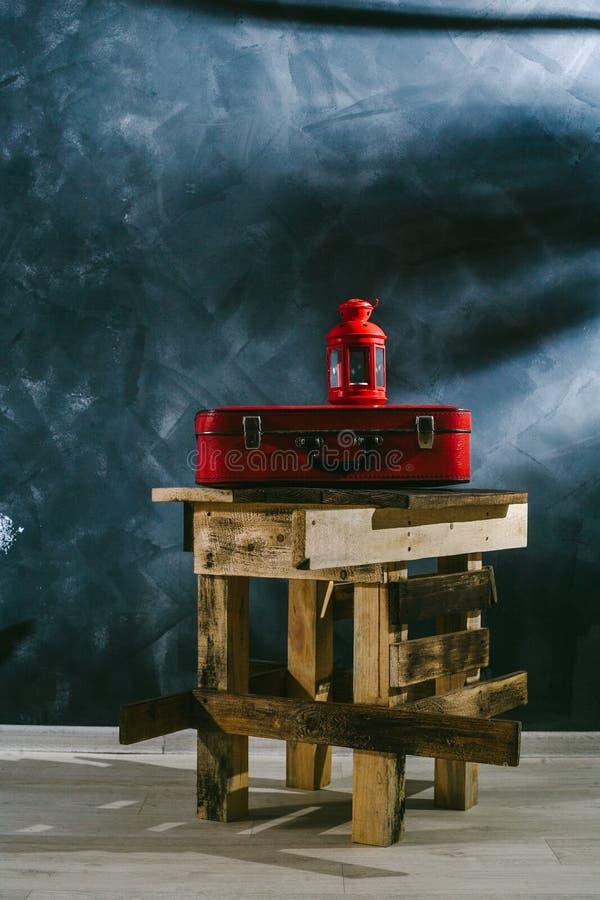Een rode koffer en een rode kandelaar op een donkere achtergrond stock afbeeldingen