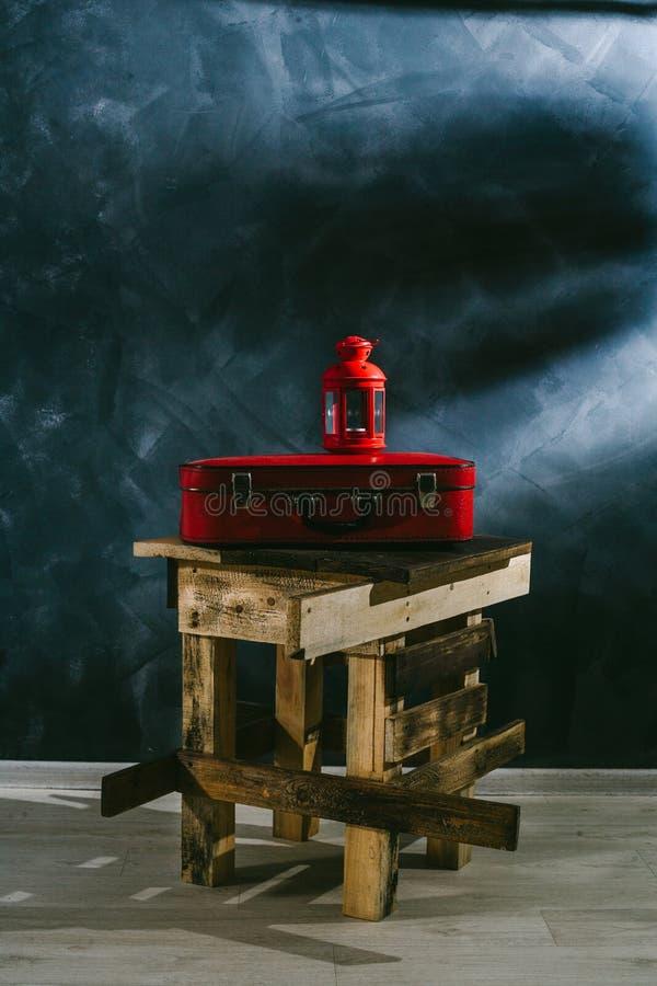 Een rode koffer en een rode kandelaar op een donkere achtergrond royalty-vrije stock foto