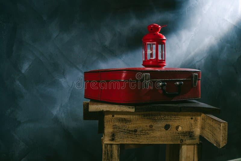 Een rode koffer en een rode kandelaar op een donkere achtergrond royalty-vrije stock afbeelding