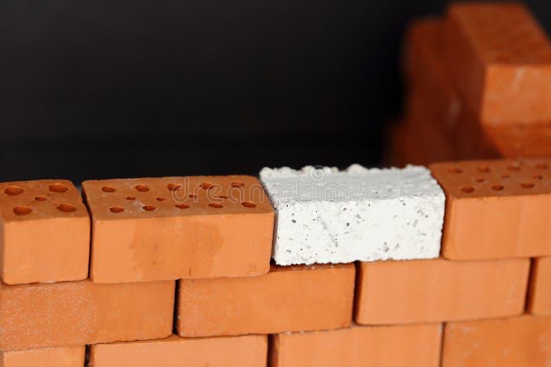 Een rode muur met één witte baksteen stock foto