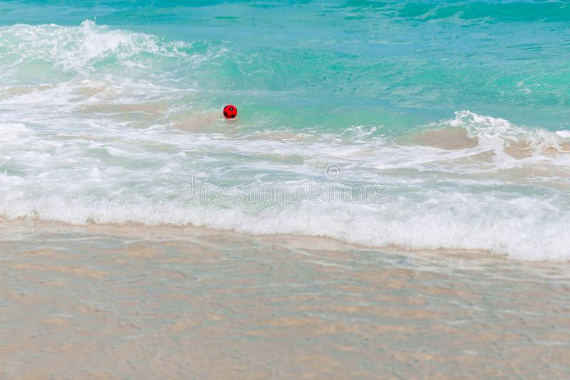 Een rode rubbervoetbalbal drijft in de oceaan De golven dragen de bal aan de kust stock foto's