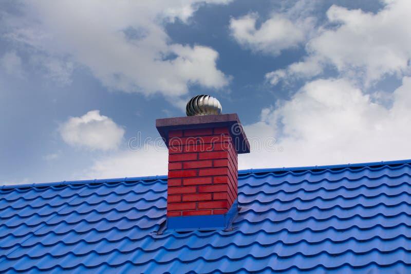 Een rode schoorsteen met met draaiende kap op een blauw metaaldak stock fotografie