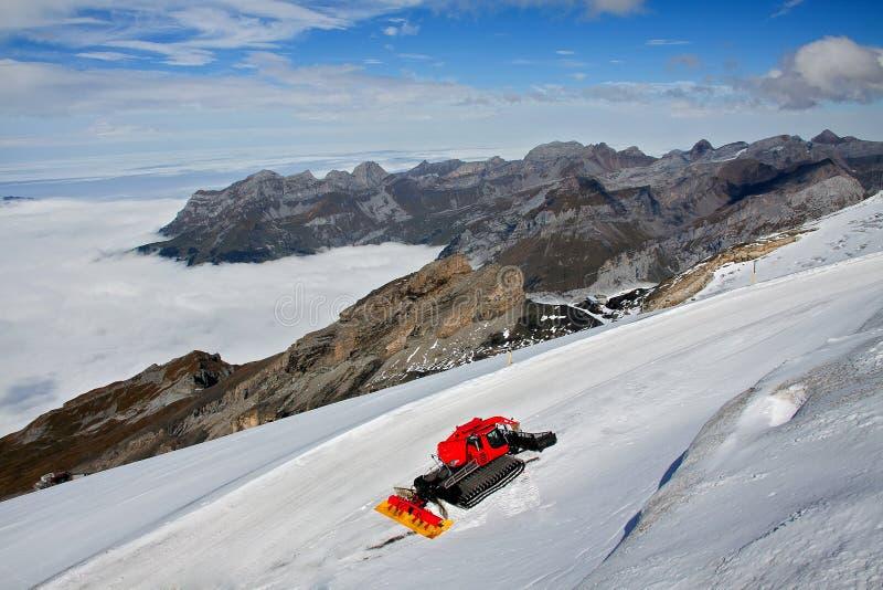 Een rode sneeuwploeg op sneeuwberg royalty-vrije stock afbeeldingen
