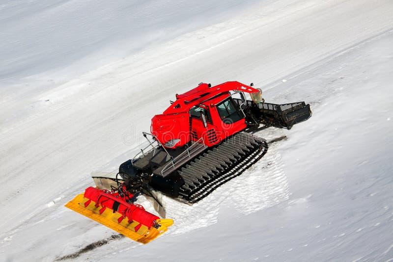 Een rode sneeuwploeg op sneeuwberg royalty-vrije stock foto