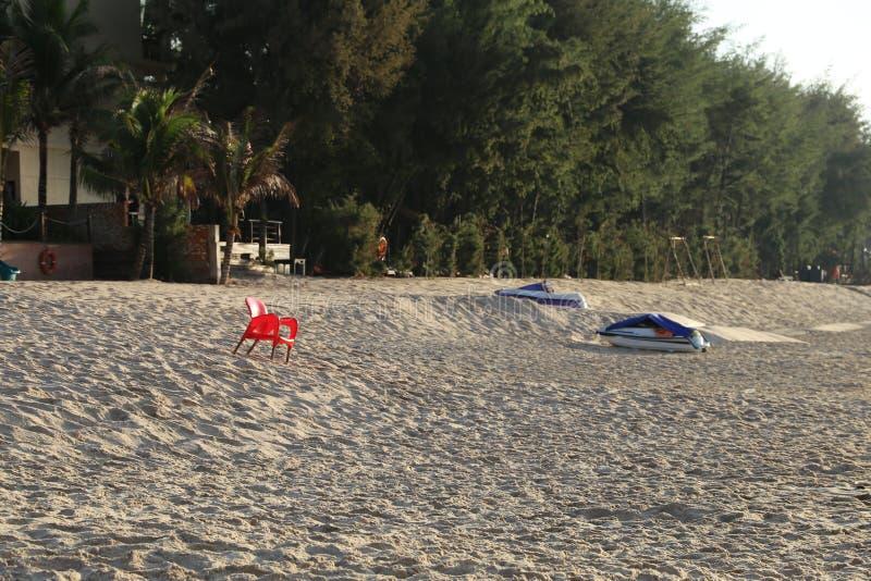 Een rode stoel op een lang wit zand royalty-vrije stock afbeeldingen