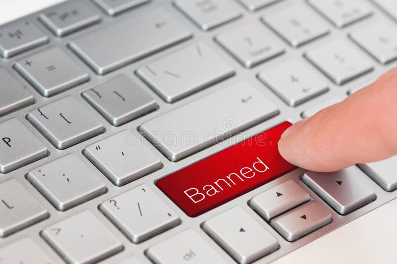 Een rode verboden knoop van de vingerpers op laptop toetsenbord stock fotografie