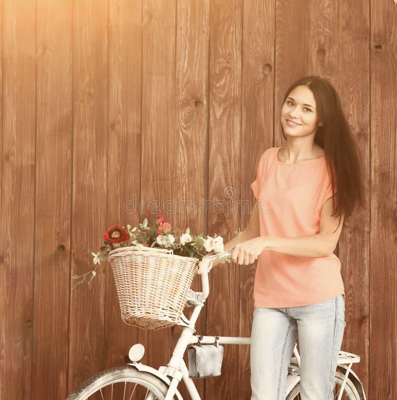 Een romantische jonge vrouw die de camera met haar fiets en een mand van wildflowers kijken De zomer stock fotografie