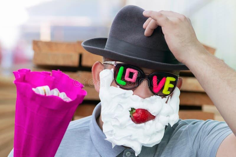 Een romantische kerel in donkere glazen met de inschrijvingsliefde, aardbeien in zijn mond en met slagroom op zijn gezicht geeft  royalty-vrije stock foto's