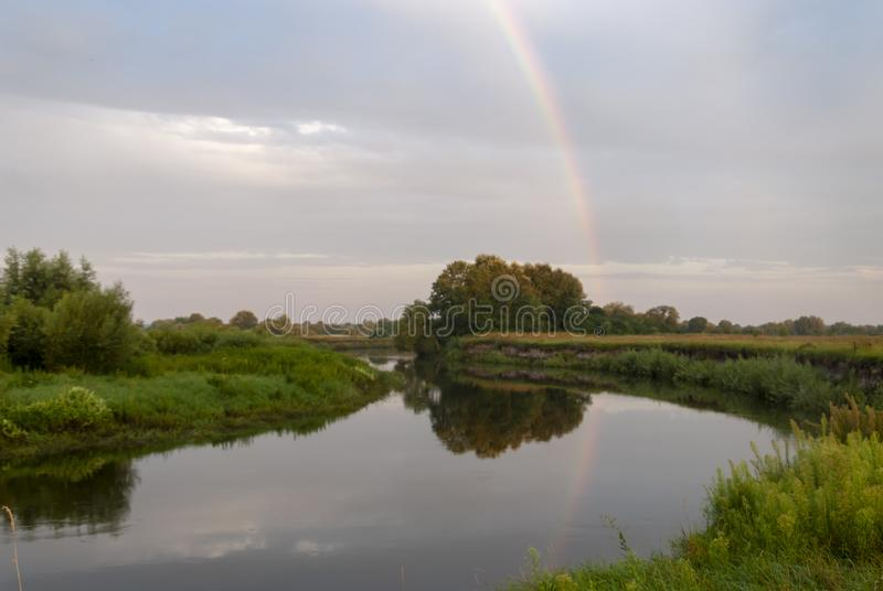 Een romantische regenboog tegen de achtergrond van een duidelijke ochtendhemel over een stille rivier royalty-vrije stock afbeeldingen