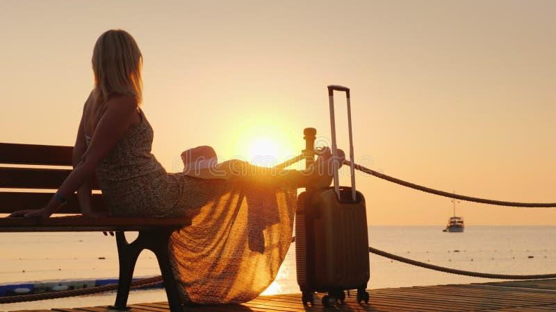 Een romantische vrouw in een lichte kleding met een forse zak zit op het dok, bekijkt de zonsopgang over het overzees en een eenz stock foto's