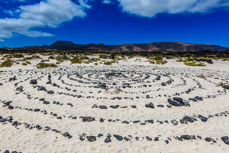 Een rond steenpatroon in het zand door een strand stock foto's