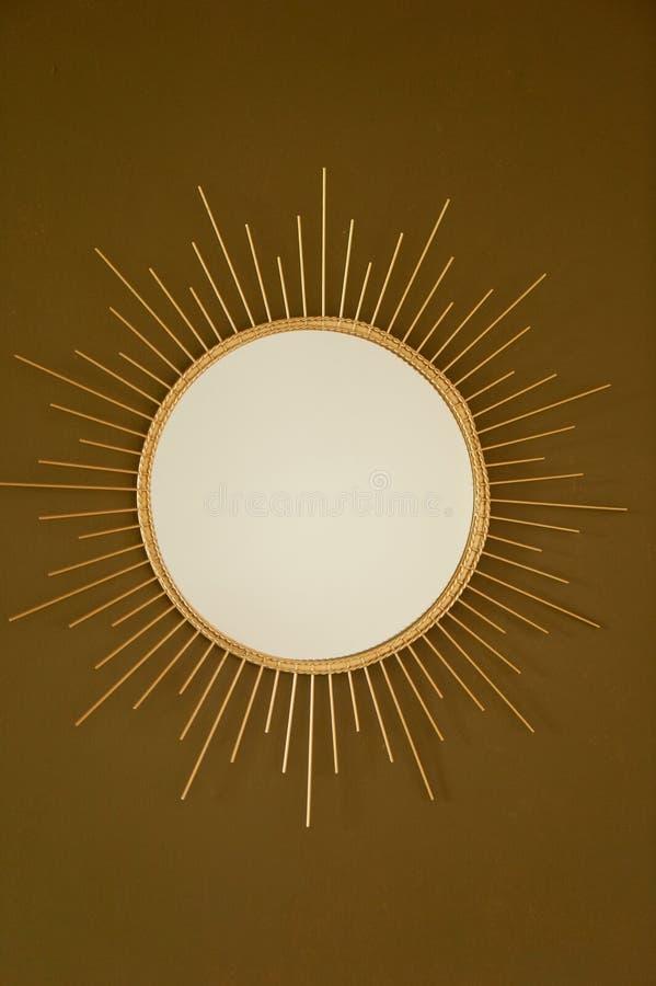 Een ronde spiegel op een bruine en gouden muur In de vorm van de zon in een Gouden metaalkader Binnenlands ontwerp stock fotografie