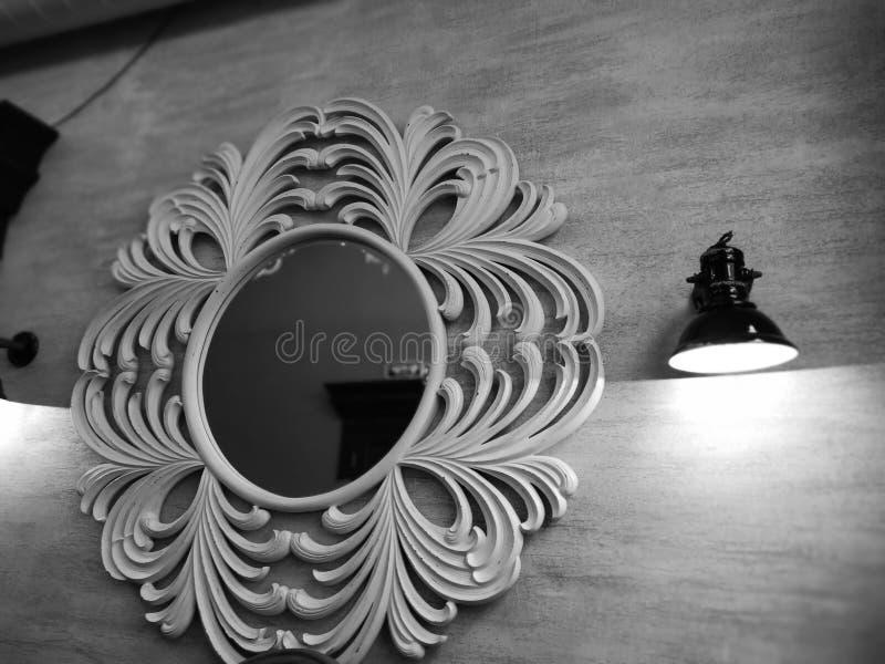 Een ronde spiegel in een openwork kader en een lamp op de muur Vint stock afbeeldingen