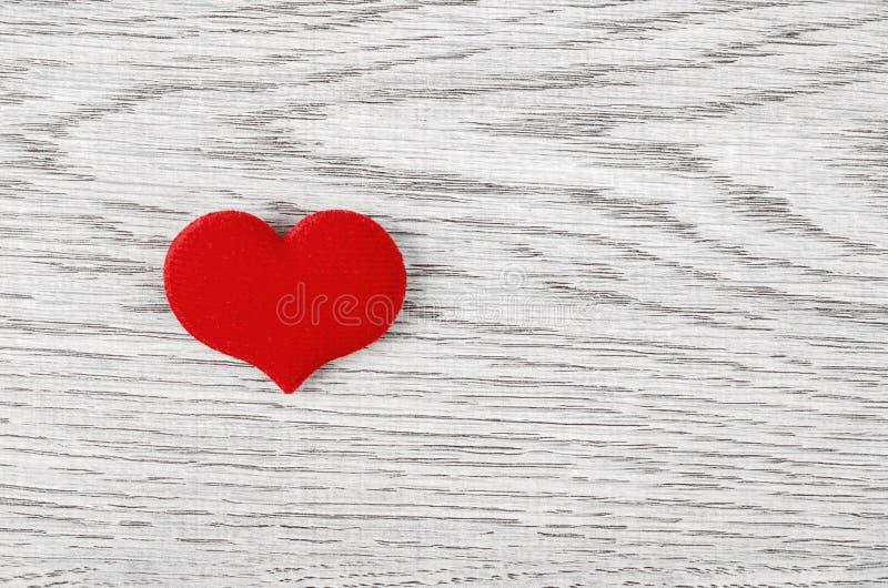 Een rood hart op houten achtergrond stock foto's