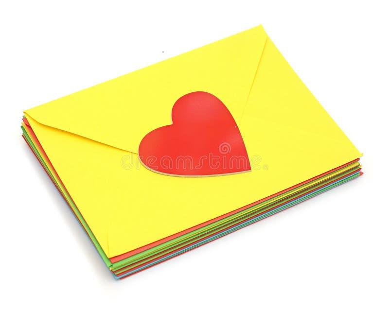 Een rood hart op stapel kleurrijke enveloppen royalty-vrije stock afbeeldingen