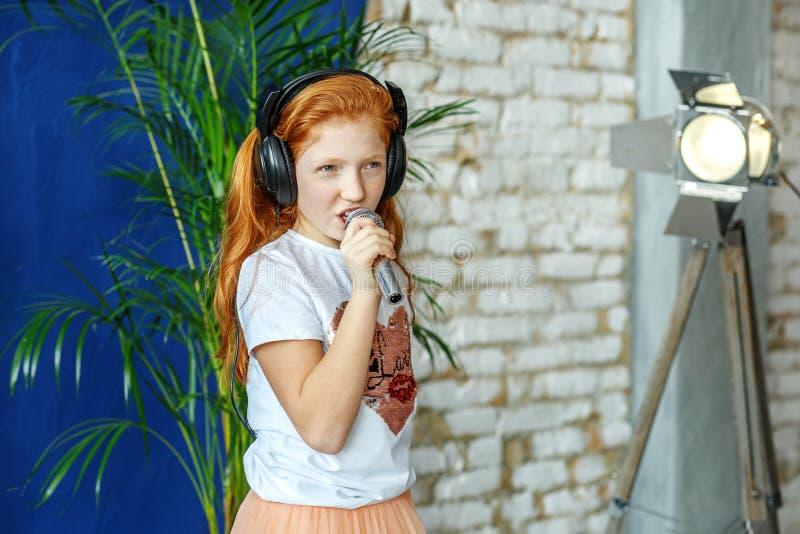 Een roodharig kind zingt een lied in een microfoon Het concept is royalty-vrije stock afbeeldingen